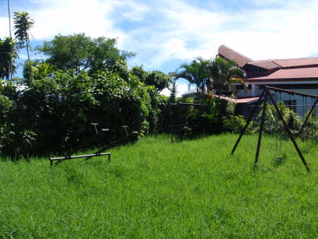 jungle gym: Rusted swings, jungle gym, and see-saw in overgrown grass in Heredia, Costa Rica. Stock Photo