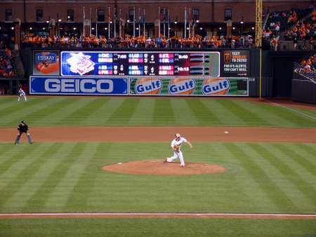Baltimore, MD - JUNE 11: Orioles pitcher Wei-Yin Chen throws ball from mound which can be seen in the airwith umpire behind him, outfielder and scoreboard June 11, 2014 in Baltimore, MD.