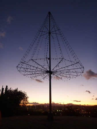 the Kaimuki Christmas tree (Metal Light Tree) on top Puu O Kaimuki (also known as Menehune Hill) at dusk on with cityscape of Oahu, Hawaii. photo