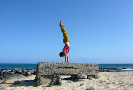 Man wearing a red t-shirt, long olive pants, and bare feet Handstands on top a old historic pillbox on the beach Sand Island Beach on Oahu, Hawaii