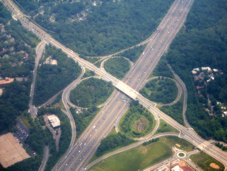 off ramp: Highway clover leaf interchange circles in Washington DC area aerial surrounded by forest.