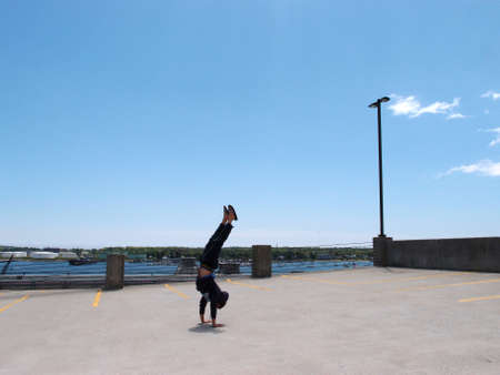 Man wearing a hoodie, pants, and slippers does Handstands on top of a parking garage the City of Portland Maine with Casco bay in the distance. photo