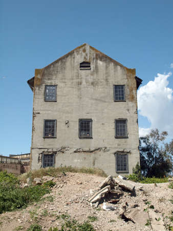 attraktion: Rundown Quartermaster building with seven windows and a blue sky on Alcatraz Island in San Francisco Bay, California.