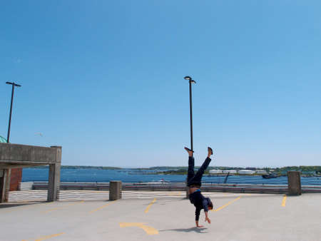 Man wearing a hoodie, pants, and slippers does one handed Handstands on top of a parking garage the City of Portland Maine with Casco bay in the distance. photo