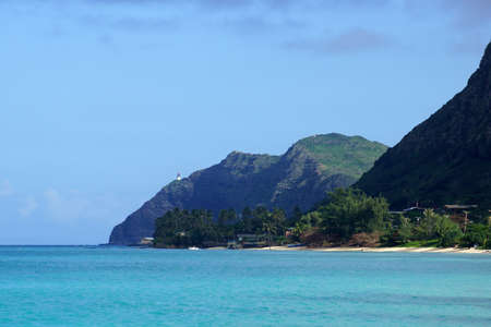 windward: Waimanalo beach, bay, and Makapuu Point with Makapuu Lighthouse visible on cliffside mountain on windward coast of Oahu, Hawaii and boat in the water. Stock Photo