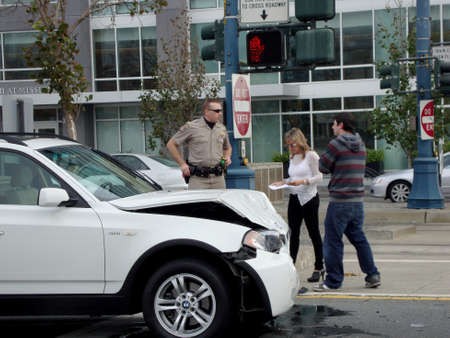 king street: SAN FRANCISCO - JANUARY 16, 2010: Highway Patrol police office assist people after their white BMW SUV is in an accident on King Street in Mission Bay, San Francisco. Editorial