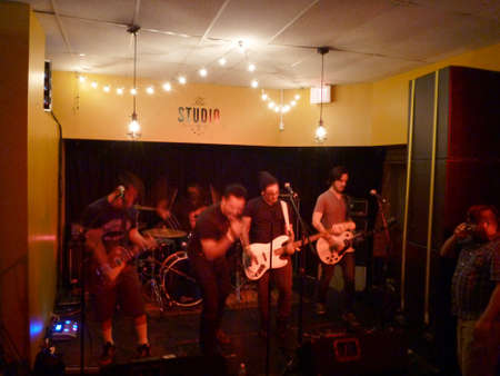 ignite: HONOLULU, HI - JUNE 21, 2014: Male Rock Band Ignite The Red jams and sings at The Studio playing guitars and drums.