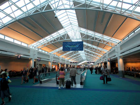 PORTLAND, OR - MAY 27, 2014: People walk to terminals with bags at PDX, Portland International Airport which is a major transportation hub in the northwest coast of USA.