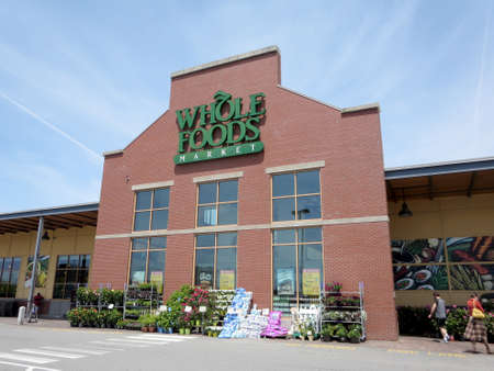 american food: PORTLAND, MAINE - JUNE 1, 2014: Whole Food Market exterior and sign on a clear day. Whole Foods is an American foods supermarket chain specializing in natural and organic foods.