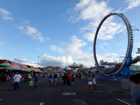 HONOLULU, HI - JUNE 28, 2014: People walk around with Rides surrounding them at the Hawaii's annual 50th State Fair with wheel of fire and swings at the Aloha Stadium parking lot.