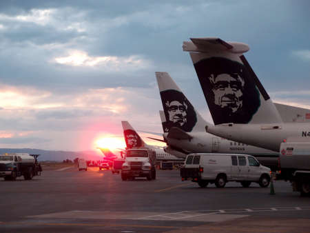 PORTLAND, OR -  MAY 27: Awesome Sunsets over row of Alaskan Airlines planes with truck and vansat Portland Internation Airport, Portland, Oregan on 27 May 2014.