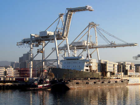 OAKLAND - NOVEMBER 14:  Matson shipping boat is unloaded by cranes in Oakland Harbor as a tugboat pushes a barge in front of it. The fourth busiest container port in the country, its a major economic engine in the San Francisco Bay Area.  November 14, 20
