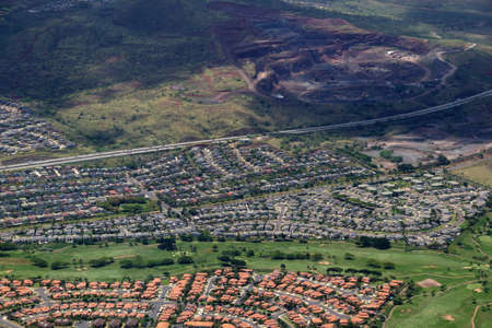 Aerial of Highway,  Kapolei homes, golf course, and quarry on the west side Oahu, Hawaii on a beautiful day.