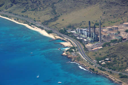 Aerial view of Kahe Point Power Plant sits along the ocean with highway road and boats in the water on the ewa side of Oahu, Hawaii.