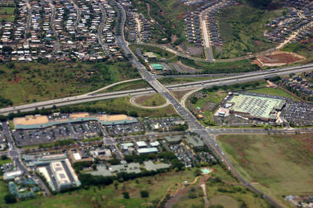 Aerial of Highway interchange, Kapolei homes, shopping centers, and quarry on the west side Oahu, Hawaii on a beautiful day.