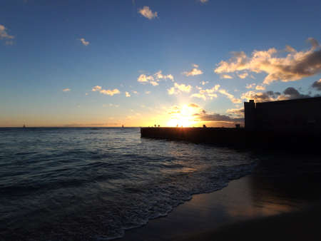 Dramatic Sunset over Natatorium wall on San Souci Beach with boats sailing on the water on Oahu, Hawaii. photo