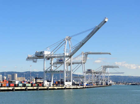 OAKLAND - FEBRUARY 22:  Row of Cargo Cranes tower over shoreline in Oakland Harbor on a nice day with Oakland and surrounding hills in the distance. The fourth busiest container port in the country, its a major economic engine in the San Francisco Bay Ar
