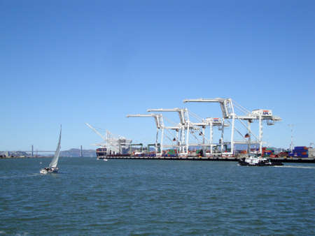 OAKLAND - MAY 23:  Cargo Cranes, tugboat and sail boat in Oakland Harbor on a nice day with San Francisco bridge and city in the distance. The fourth busiest container port in the country, its a major economic engine in the San Francisco Bay Area.  May 2