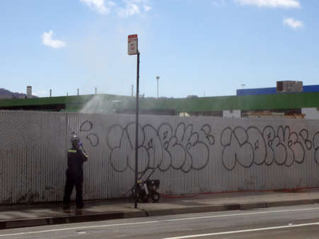 SAN FRANCISCO - MAY 31: Man uses painting machine to paint over graffiti tagging on fence along road in  San Francisco, California, May 31, 2011