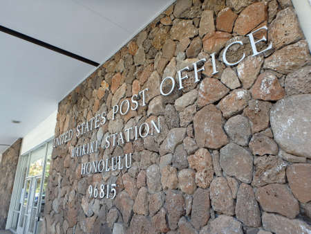 HONOLULU - JULY 25: Metal letters that spell United States Post Office, Waikiki Station, Honolulu, 96815 by entrance, fastened on lava rocks on the side of a building. Waikiki, Hawaii July 25, 2014