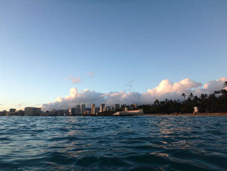 Dramatic Dusk scape over historic Natatorium, Waikiki and San Souci Beach with people on the beach, coconut trees and lifeguard tower on a nice day Oahu, Hawaii. photo