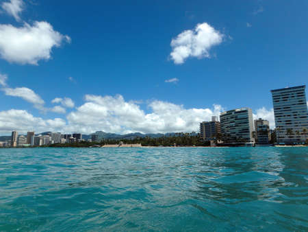 Historic Natatorium, Waikiki, Condomiums, Honolulu cityscape and San Souci Beach, coconut trees and lifeguard tower on a nice day Oahu, Hawaii seen from the water.