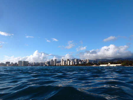 Historic Natatorium, Waikiki, Honolulu cityscape and San Souci Beach, coconut trees and lifeguard tower on a nice day Oahu, Hawaii seen from the water.  photo