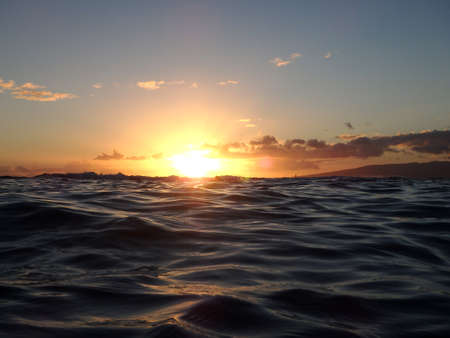 Dramatic lighting the sky and ocean during sunsets with light reflecting on ocean waves moving with boats sailing on the water off Waikiki with clouds on Oahu, Hawaii.  photo