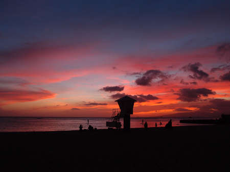 boarders: Dramatic sky lighting of dusk on Kaimana Beach with stand-up paddle boarders and lifeguard stand in Waikiki  on Oahu, Hawaii. Stock Photo