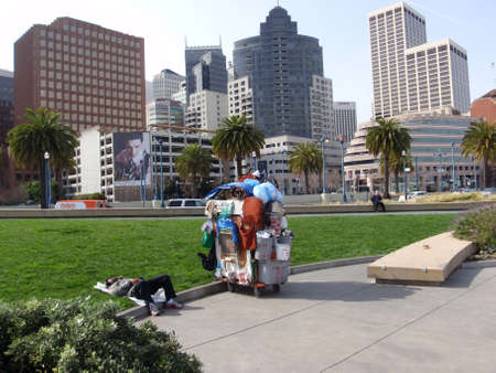 SAN FRANCISCO - FEBRUARY 18: Homeless man sleeps with homemade shopping carts filled with buckets, clothes, a chair and various other things along the Embarcadero with Downtown buildings in the background in San Francisco California, February 18, 2009