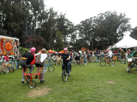 SAN FRANCISCO - SEPTEMBER 24:  people ride crazy bicycles in circles in celebration of bicycling at Tour De Fat concert with stage and trees in the distance taken September 24, 2011 Golden Gate Park San Francisco.