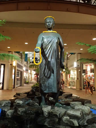 MAUI - SEPTEMBER 29: Hawaiian Queen Kaahumanu Statue stand above waterfall in Mall named after her as people wander around mall on September 29, 2014  Kahului, Hawaii. 新聞圖片
