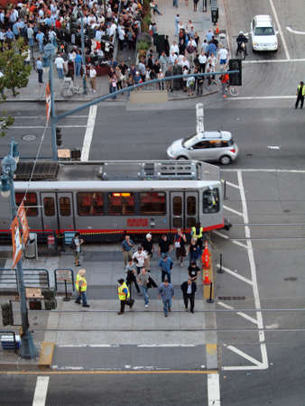 SAN FRANCISCO, CA - SEPTEMBER 28: Aerial view of crowd of people crossing street to get to ballpark as MUNI train and cars move along King street as it intersects with Second Street and people hang out at MOMA bar on September 28, 2010 AT&T Park San Franc