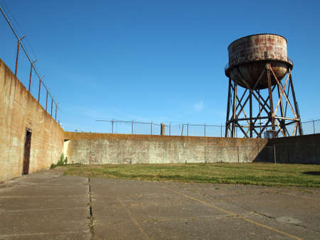 prison yard: Rusting water tower stands beyond the wall  and bard wire fence of Alcatrazs prison yard.