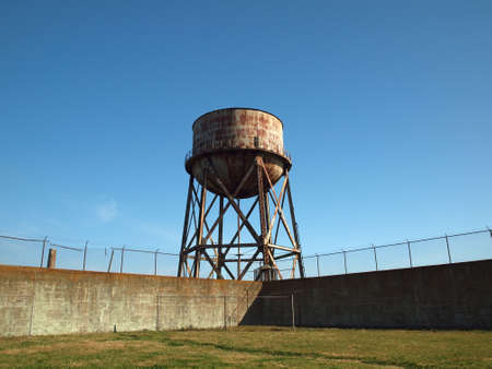 Rusting water tower stands beyond the wall  and bard wire fence of grassy Alcatrazs prison yard. Editorial