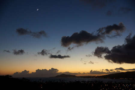 sliver: Hawaii Kai and Diamond Head at Night Fall on Oahu, Hawaii with moon sliver overhead. Stock Photo