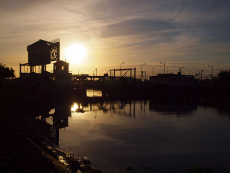 Sunset over historic 4th bridge with sun reflecting on Mission Creek and bird flying in the air in San Francisco. photo