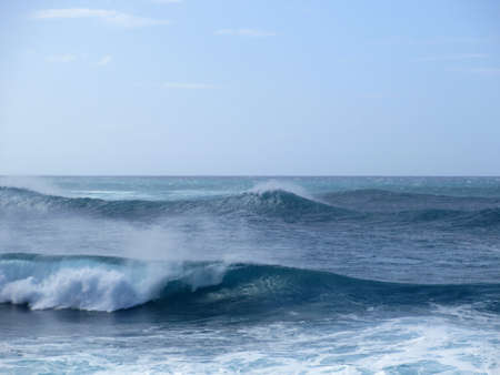 Waves break and crash towards the shore with dramatic blue sky on the North Shore of Oahu, Hawaii. Stock Photo
