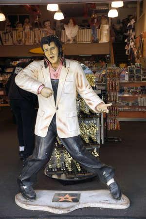 baile caricatura: LOS ANGELES, EE.UU. - 23 de enero 2014: R�plica de Elvis Presley cantando en una tienda de souvenirs con estatuas oscar detr�s de �l en el bulevar de Hollywood.