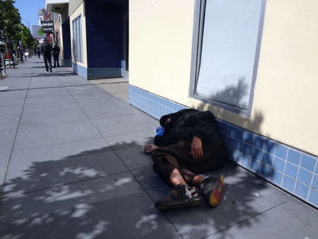 homeless person: SAN FRANCISCO - JUNE 23: homeless person sleep in shade of tree on sidewalk to avoid the sun with people walking in the distance mid-day in San Francisco.  June 23, 2011.