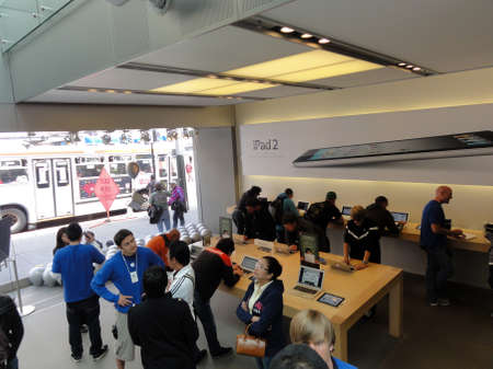 SAN FRANCISCO, CA - JUNE 27: People look at products and talk to sales reps inside Apple Store with Ipad 2 ad on wall in San Francisco California June 27 2011.