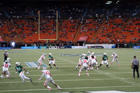 end of rainbow: HONOLULU, HI - NOVEMBER 22: UNLV vs. UH: UH quarterback sets to throw ball as players scrabble to get open during play of college football game at night. taken on November 22, 2014 at Aloha Stadium in Honolulu, Hawaii.