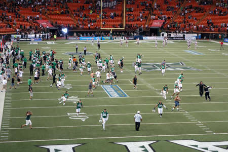 hustle: HONOLULU, HI - NOVEMBER 22: UNLV vs. UH: University of Hawaii players and fans rush on the field to celebrate win before game is official over at night (fans and players were forced to return to off the field so game could be complete). taken on November  Editorial