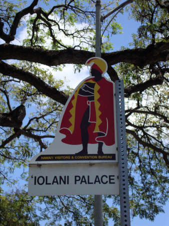 opulent: Iolani Palace Street Sign Marker on Oahu, Hawaii with tree branch, a blue sky with clouds. Iolani Palace is the only royal palace in the USA.