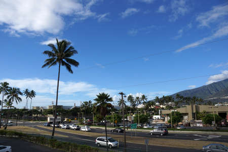 intersect: KAHULUI, MAUI - OCTOBER 2: Cars travel along busy intersect with Queen Kaahumanu Center in the distance on a beautiful day on October 2, 2014 Maui. Editorial