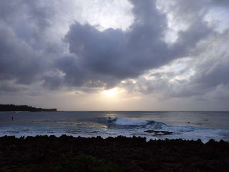 Surfers ride waves as sunsets though the clouds off the coast of Turtle Bay on the North Shore of Oahu, Hawaii. photo