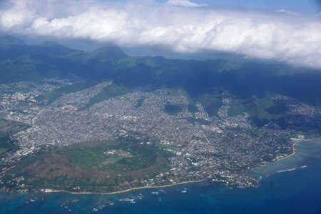bird       s house: Aerial of Diamond Head Crater, Kaimuki, Kahala, and Honolulu with clouds hanging over the mountains on nice day. November 2014. Stock Photo