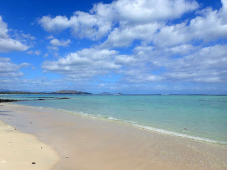 windward: Beach next to Pahonu Pond (Ancient Hawaiian Fishpond) with Shallow wavy ocean waters of Waimanalo bay looking into the pacific ocean with a blue sky full of clouds on Windward Oahu 2015.