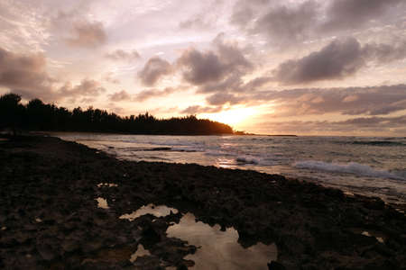 Sunset through the clouds and reflecting on the waves as they break on rocky shore with tide pools at Kawela Bay on the North Shore of Oahu. photo