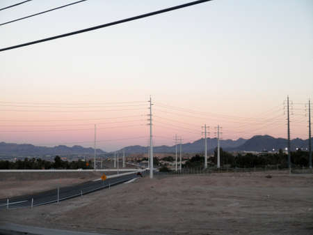 High Voltage Power-lines and Highway on-ramp at dusk in Las Vegas, Nevada.